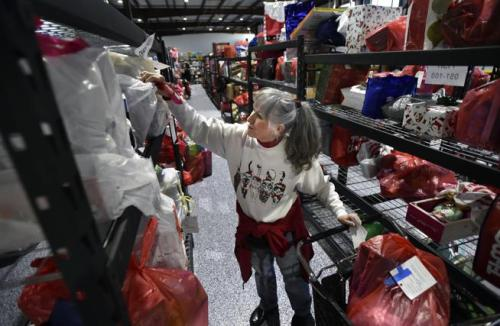 Aziel, 3, grabs a wooden toy from a bin during the annual A Precious Child giveaway on Tuesday in Broomfield.