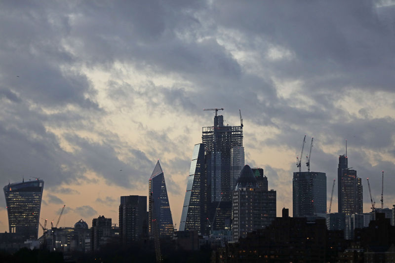 © Reuters. The sun sets behind the Canary Wharf financial district of London