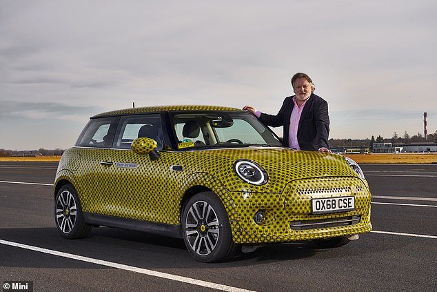 Getting behind the wheel: Ray Massey pictured with the heavily camouflaged pre-production electric Mini ahead of his exclusive road test