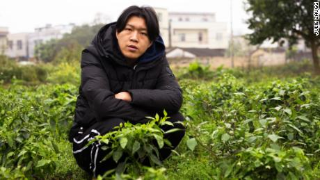 Wu Nengji poses on the rural pig farm from where he streams mini movies across China.
