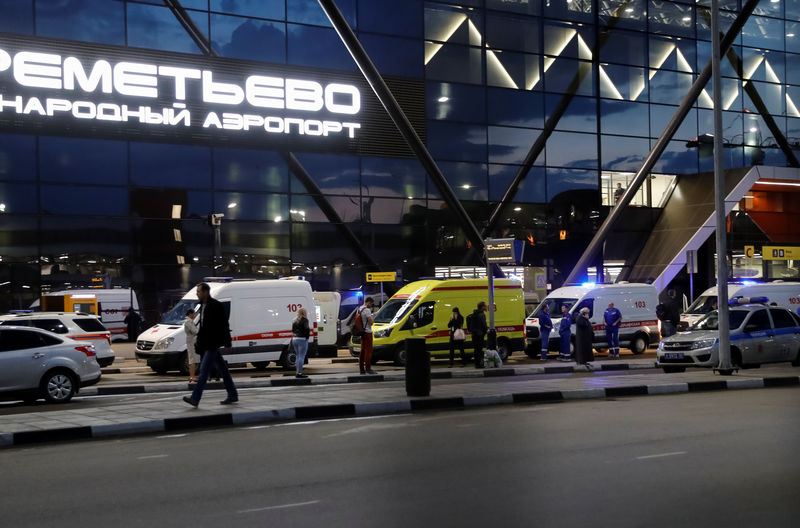 © Reuters. Ambulances wait in front of the terminal building after a passenger plane made an emergency landing at the Sheremetyevo Airport outside Moscow