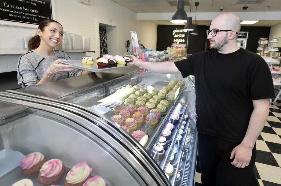 Brenda DePonte, left, co-owner of Sugar Bakery in East Haven, offers a cupcake sample Thursday afternoon to regular customer Maltoo Abdel of Meriden. Photo: Peter Hvizdak / Hearst Connecticut Media / New Haven Register