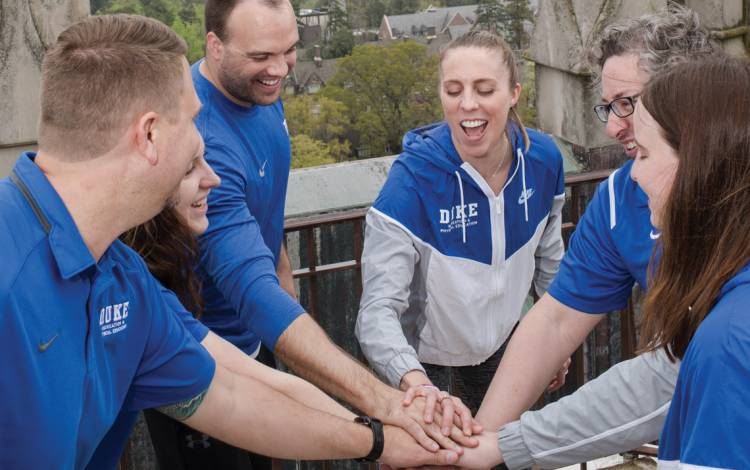 Duke Recreation & Physical Education staff members cheer after climbing 239 steps to the top of Duke University Chapel.