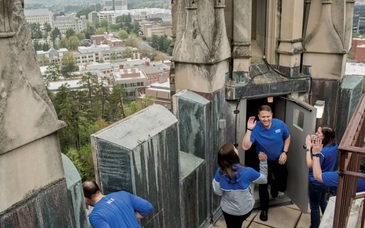 Brooke Povich, left, and Leslie Douglas, right, give high fives to Nathan McKinnis at the top of Duke University Chapel.
