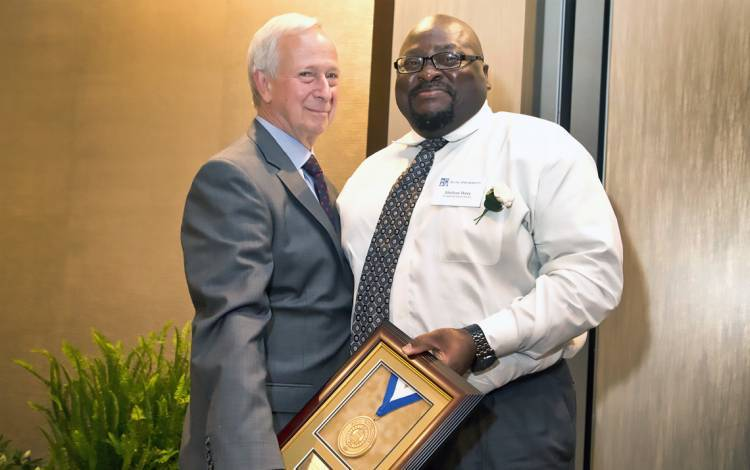Shelton Perry, right, receives the Presidential Award from former President Richard H. Brodhead.