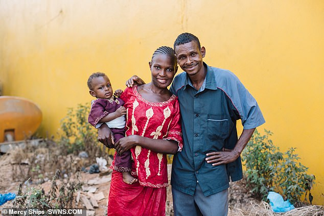 Isatu (pictured with her baby son and another relative) endured three surgeries to remove her tumour, replace her jaw with a bone graft and smooth out her skin in a cosmetic procedure