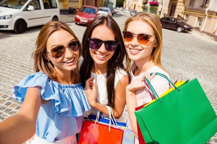 Three women with shopping bags taking a selfie.