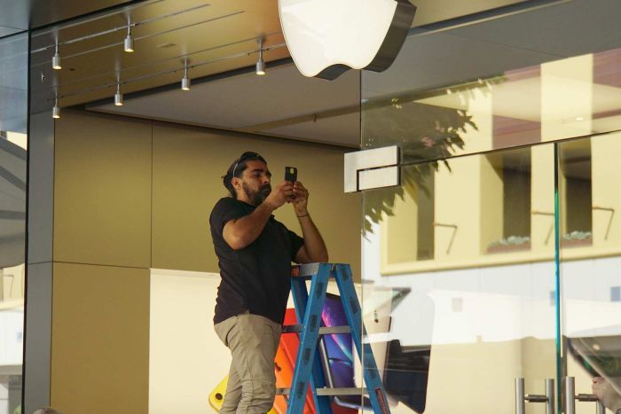 A man stands on a ladder taking a picture with a phone at the Apple Perth City store entrance with an Apple logo above him.