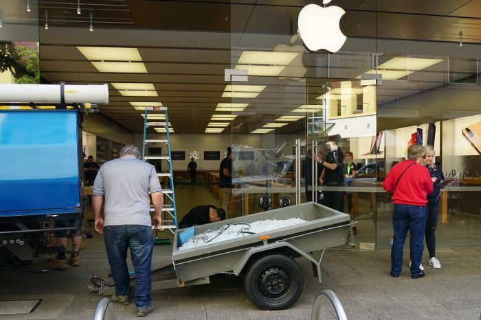 A wide shot showing people and a trailer filled with broken glass outside the Apple Perth City store with a big window missing.