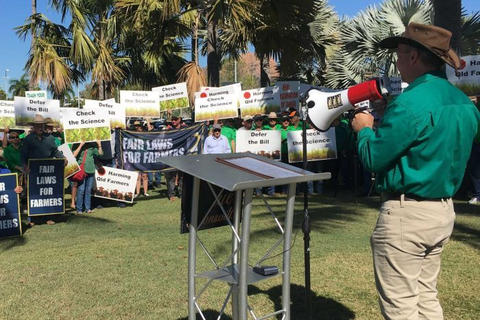 A man with a megaphone stands in front of a crowd people holding placards at a protest.