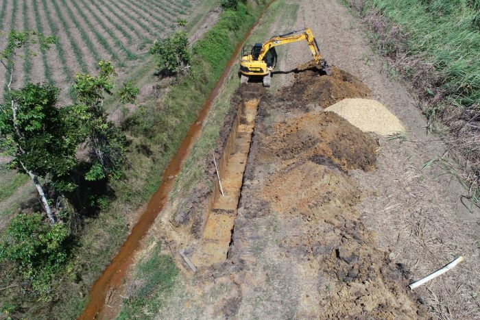 A mechanical digger digs out a long trench in a paddock.