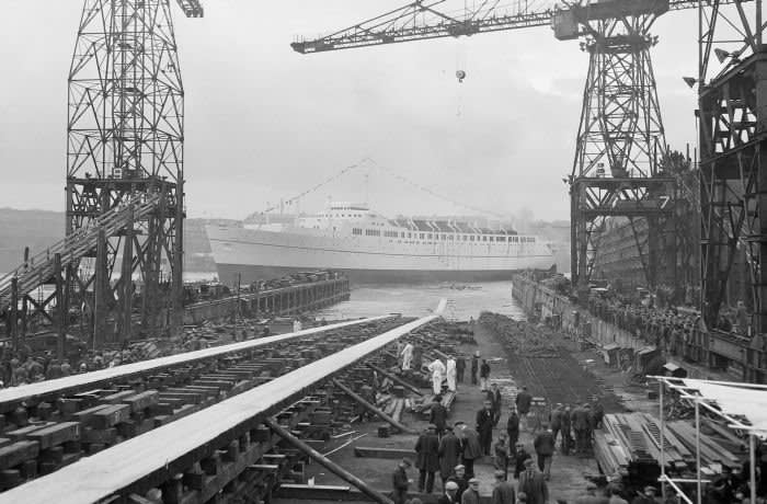 Industry, Ship Building, Newcastle on Tyne, England, 10th May 1953, The 26,000 ton cruise liner the 'Empress of England' is launched from the slipway of the ship yard, Hundreds of ship workers and labourers line the slipway to watch (Photo by Popperfoto via Getty Images/Getty Images)