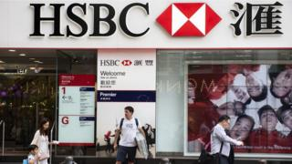 Pedestrians are seen walking past a branch of HSBC bank in Causeway Bay