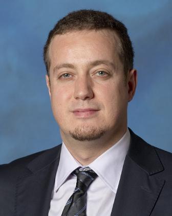 Headshot of Murat Akcakaya, against a blue background.