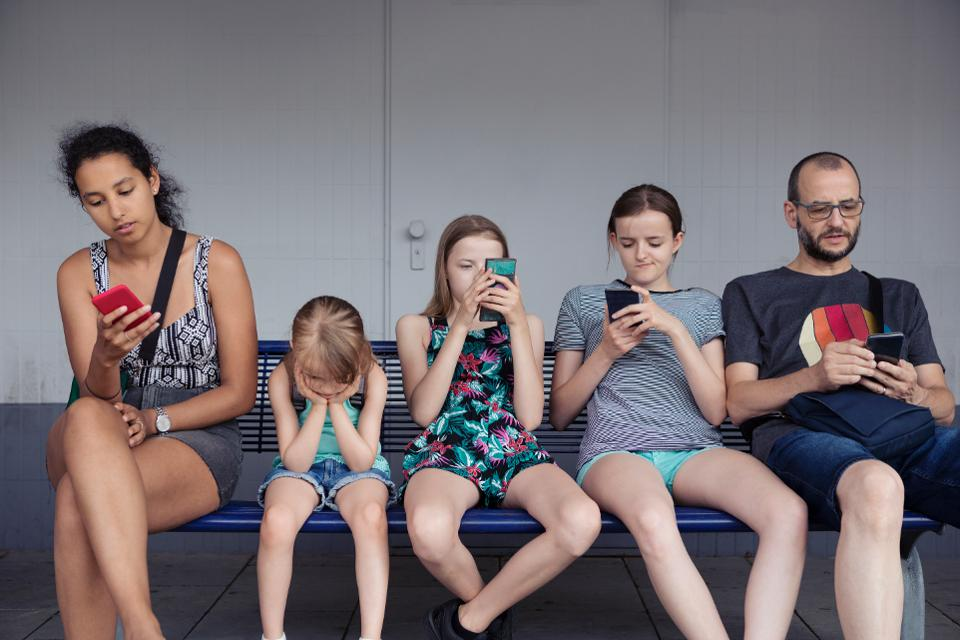 Adults and children sitting on a bench distracted by mobile phones whilst younger child without a phone is completely fed up