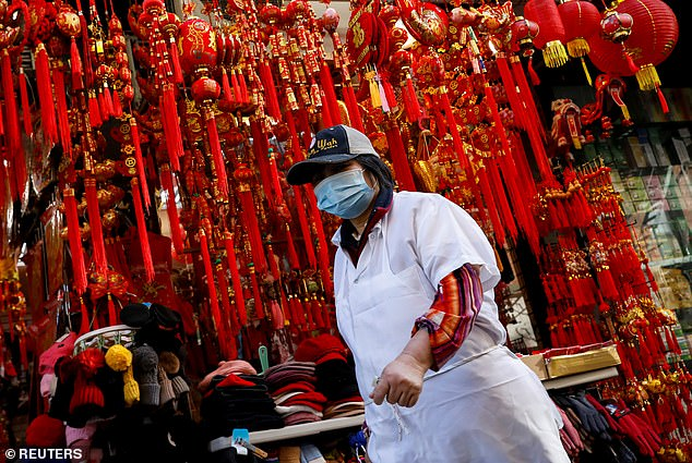 Four people are in isolation in New York being tested for coronavirus - one of which has come back negative and three that are pending. Pictured: A worker wears a mask in Manhattan's Chinatown district of New York City on Friday
