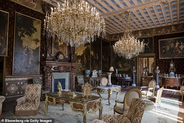 Chandeliers hang over armchairs and tables as 19th century portraits in ornate frames adorn the walls of a sitting room inside the Villa Les Cedres
