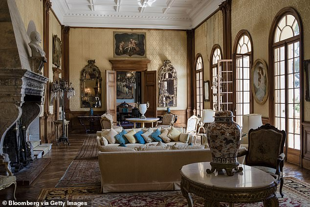Cushions rest on sofas as 19th century portraits in ornate frames adorn the walls of the 187-year-old sitting room