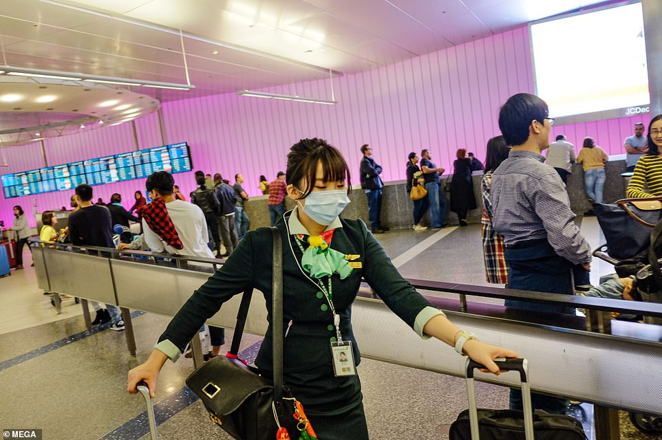 Screenings are also in place at Los Angeles International Airport. A staff member is seen wearing a face mask at LAX on Frida