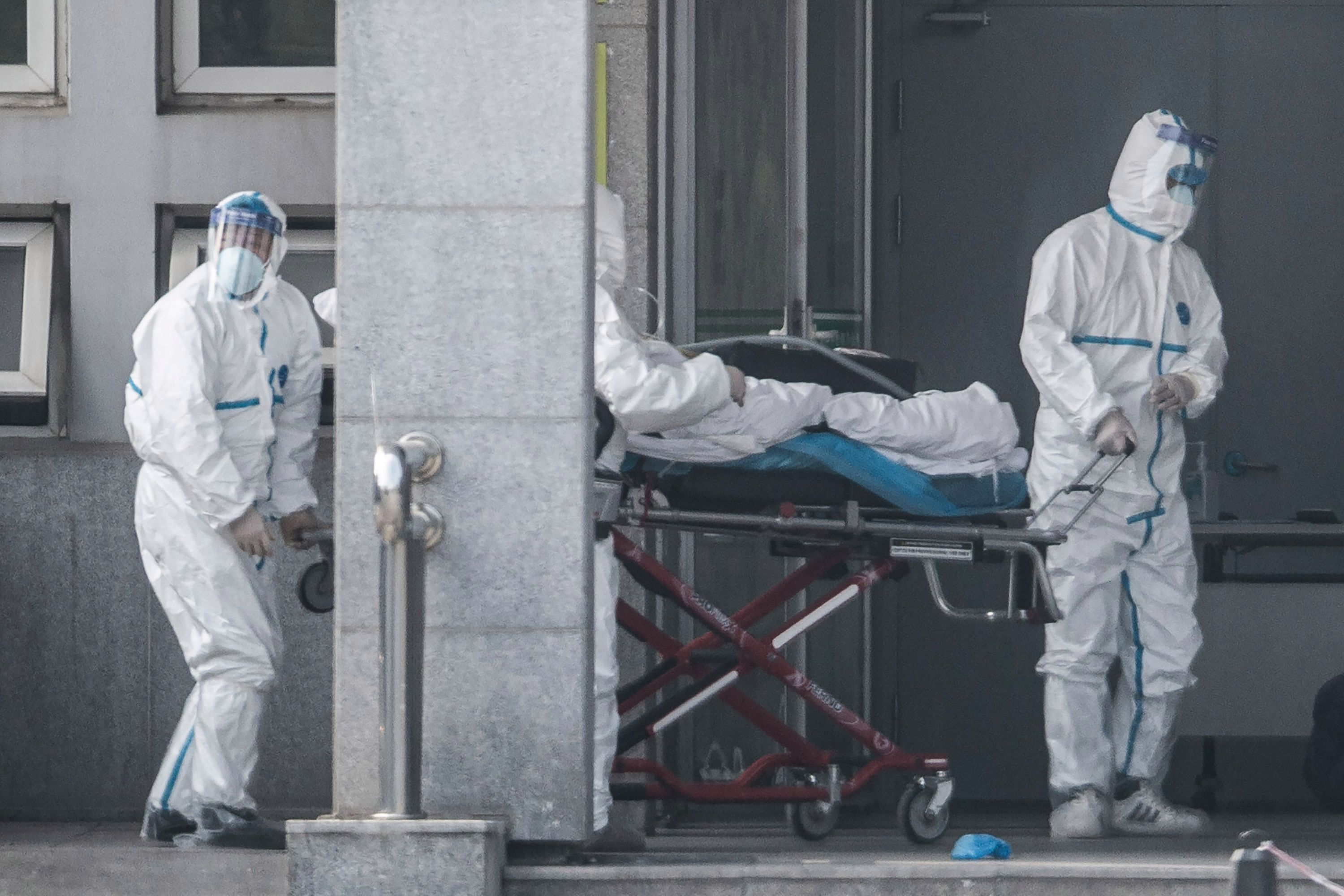 Medics in protective suits carry a patient into Jinyintan hospital in Wuhan