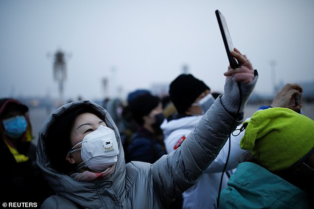 Chinese social media users have been attempting to skirt censors as they critique President Xi over his response to the coronavirus outbreak by referring to him as 'Trump'. Pictured: A woman wearing a face mask uses her cellphone at the Tiananmen Square in Beijing on Monday
