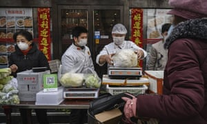 Chinese vendors wear protective masks as they sell vegetables in the street during the Chinese New Year holiday on 26 January in Beijing.