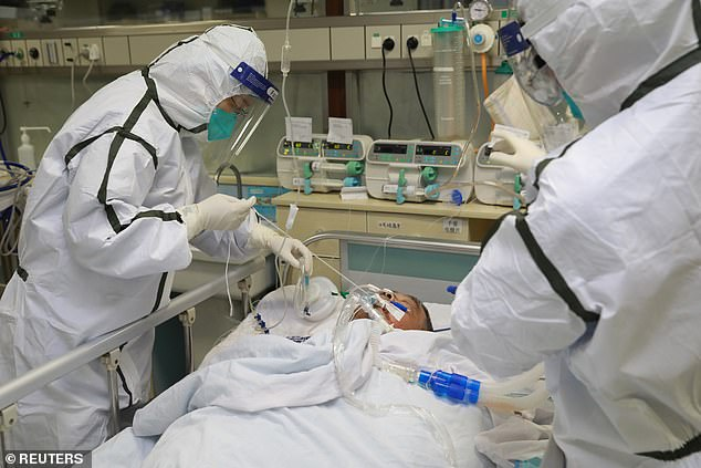 Coronavirus patients are deliberately spitting at health care workers to try and spread the killer disease, it has been claimed. Pictured, a patient at the Zhongnan Hospital of Wuhan University being treated by medical staff in protective suits