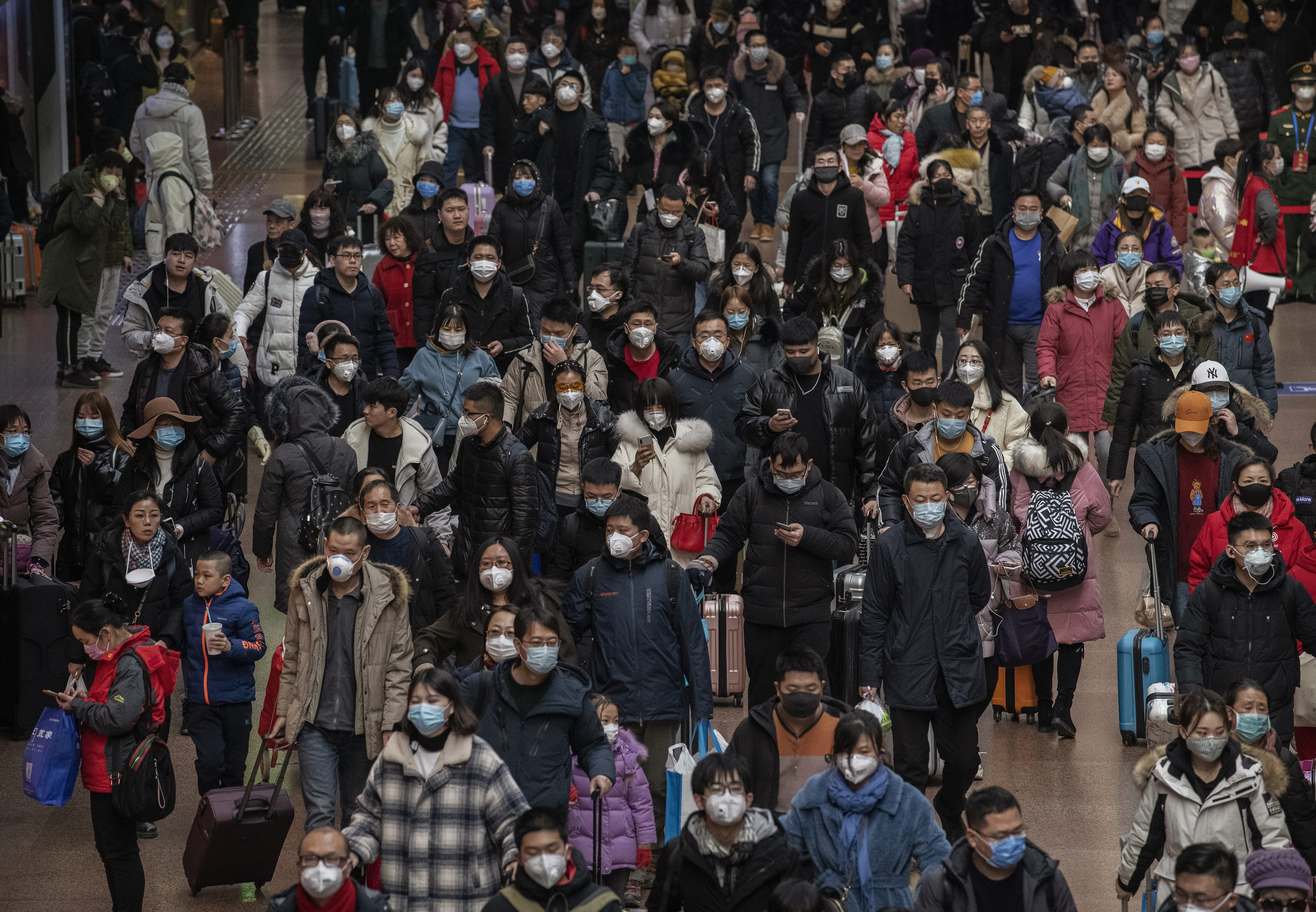 Chinese passengers, most wearing masks, arrive to board trains before the annual Spring Festival at a Beijing railway station amid the coronavirus outbreak