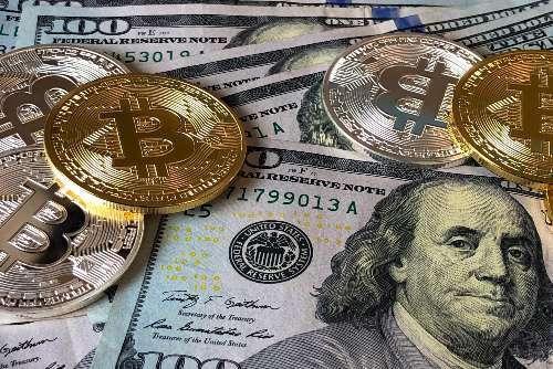 bitcoins on top of US dollar bills