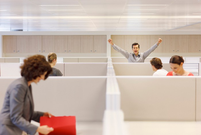 A man in an office cubicle cheering as his colleagues go about their work