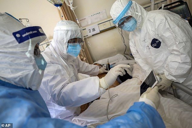 Health care workers monitor the condition of a coronavirus patient. Understanding the virus's structure, they hope, will help scientists find treatments and vaccines more quickly