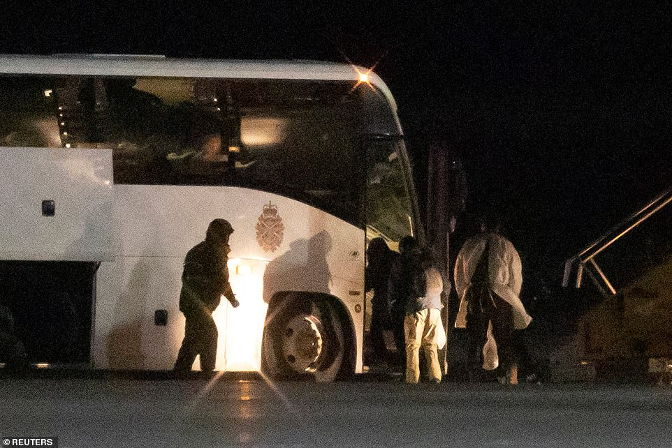 Canadian passengers evacuated from the Diamond Princess are pictured getting on a bus after landing at an air force base in Ontario