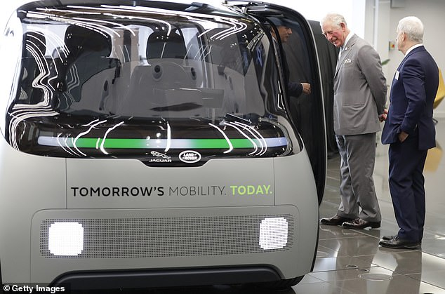 The Prince of Wales looks at the autonomous vehicle during a visit to open the National Automotive Innovation Centre