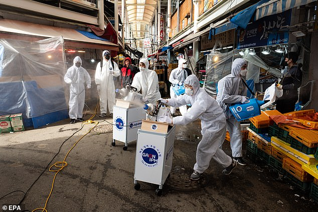 It also broadened faster than Ebola because coronavirus can spread via air while Ebola spreads via bodily fluids. Pictured: Medical personnel work in the ICU of a hospital designated for coronavirus patients in Wuhan, February 24