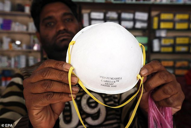 There are two common types of face masks, standard surgical face masks andN95 respirators while filter airborne particles. Pictured:A vendor in India shows an N95 mask at medical store, February 7