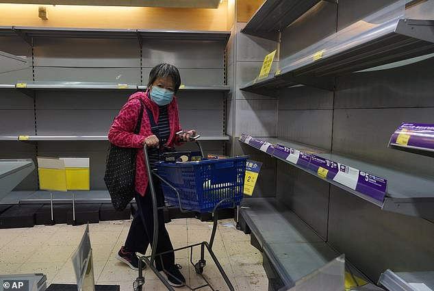 Several retailers throughout the US have either run low or completely run out of face masks, and HHS Secretary Alex Azar says the country needs 300 million masks. Pictured:A woman wearing a face mask walks past empty shelves n Hong Kong, February 6