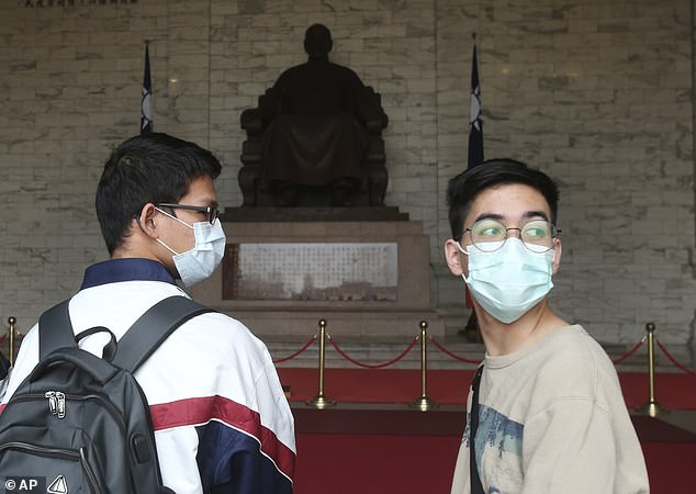 Most experts say that while masks lower the risk of viral transmission, they can't entirely prevent it. Pictured: People wear face masks at Chiang Kai-shek Memorial Hall in Taipei, Taiwan, February 27