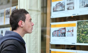 A young person looks at property in an estate agent's window