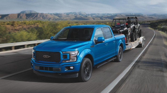 A blue 2020 Ford F-150, a full-size pickup truck, towing a trailer.