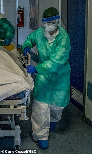 Pictured, an Italian nurse in full protective clothing, including disposable apron, trousers, shoe covers and gloves, a tight face mask and a protective visor over the face
