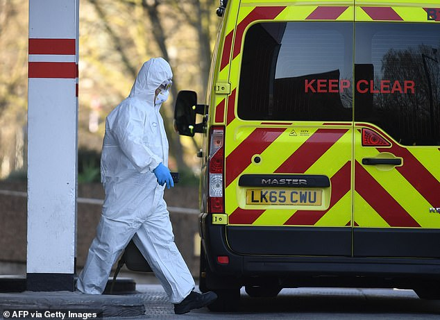 A member of the ambulance service wearing personal protective equipment is seen leading a patient (unseen) into an ambulance at St Thomas' Hospital in London on March 24, 2020
