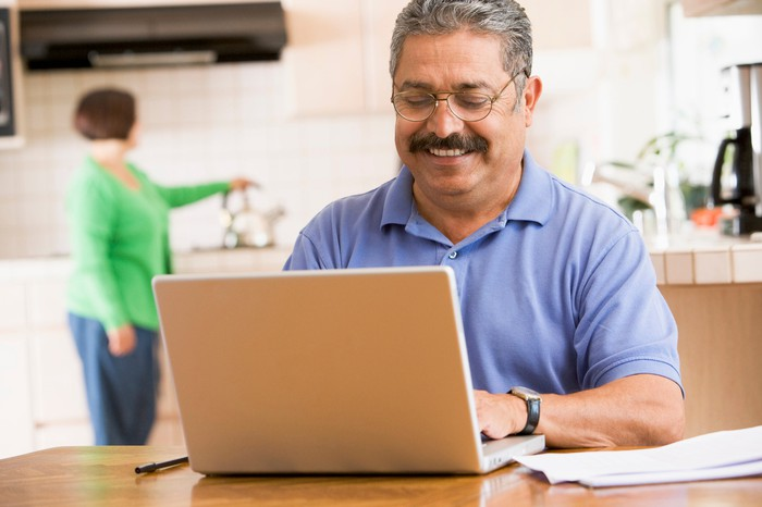 A man using a laptop at the kitchen table smiling while a woman puts on a kettle in the background.