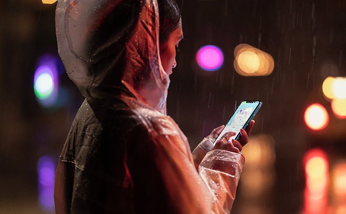 A woman looking at an iPhone at night.